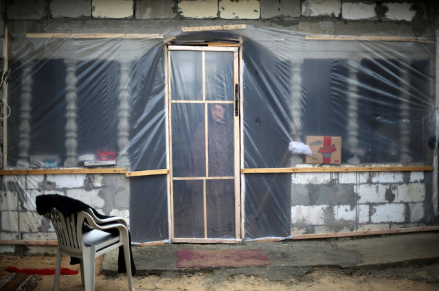 A Palestinian woman looks through her dwelling covered with plastic sheet  in Khan Younis in the southern Gaza Strip December 19, 2016. (Photo by Ibraheem Abu Mustafa/Reuters)