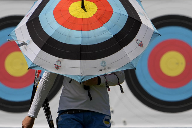 An athlete from Ukraine walks to the firing area as she practices for the 2020 Summer Olympics at Yumenoshima Park Archery Field, Sunday, July 18, 2021, in Tokyo. (Photo by Charlie Riedel/AP Photo)