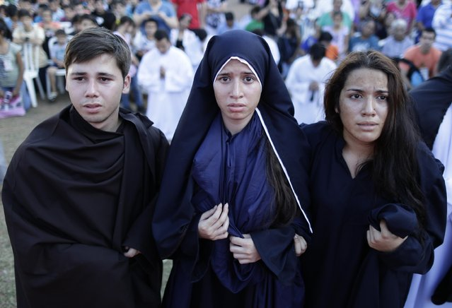 A woman plays the role of Jesus' mother, center, along with other members of Domingo Savio church as they reenact the death of Jesus during a Good Friday procession in Fernando de la Mora on the outskirts of Asuncion, Paraguay, Friday, April 3, 2015. Good Friday recalls Jesus' death by crucifixion. (Photo by Jorge Saenz/AP Photo)