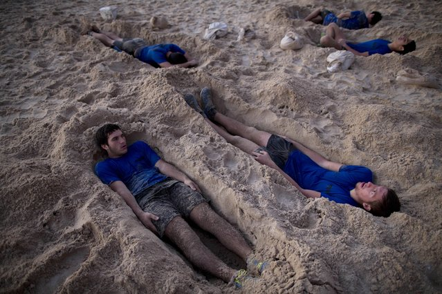 In this Thursday, March 5, 2015 photo, Israeli high-school seniors preparing to join the Israeli military later this year lie in foxholes during privately run military combat fitness training in Shefayim, central Israel. (Photo by Oded Balilty/AP Photo)