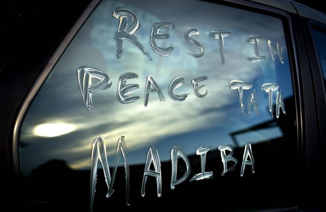 "A message using Nelson Mandela's clan name ""Madiba"" and a term of affection ""Tata"" meaning ""father"" is scrawled on the window of a car parked in the street outside Mandela's old house in Soweto, Johannesburg, South Africa, on December 6, 2013. (Photo by Ben Curtis/Associated Press)"