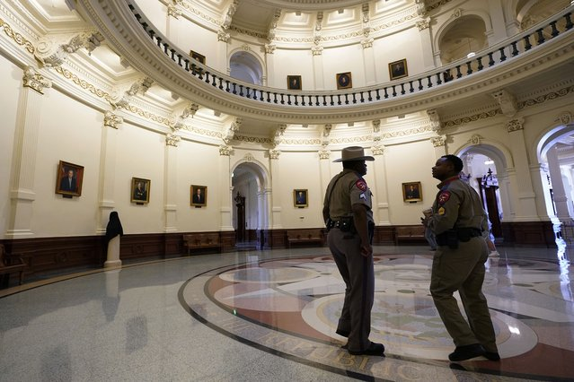 Texas Department of Safety officers stand watch over the Texas Capitol, Wednesday, August 11, 2021, in Austin, Texas. Officers of the Texas House of Representatives delivered civil arrest warrants for more than 50 absent Democrats on Wednesday as frustrated Republicans ratcheted up efforts to end a standoff over a sweeping elections bill that stretched into its 31st day. (Photo by Eric Gay/AP Photo)