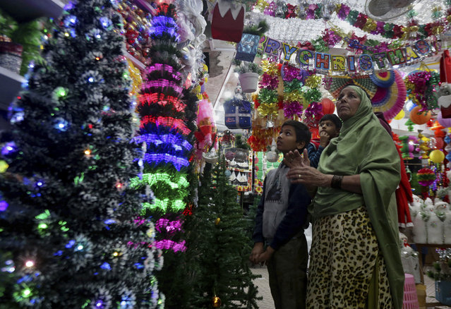 A Christian family browses Christmas ornaments to decorate their home for upcoming Christmas celebrations, at a shop in Lahore, Pakistan, Friday, December 14, 2018. (Photo by K.M. Chaudhry/AP Photo)
