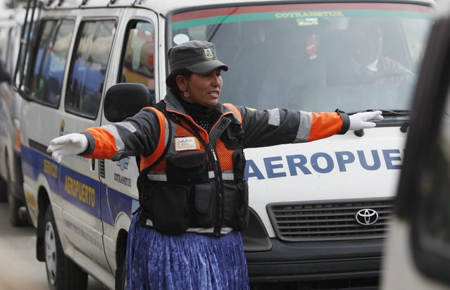 In this December 13, 2013 photo, an Aymara woman uses hand-and-arm signals to direct traffic in El Alto, Bolivia. (Photo by Juan Karita/AP Photo)