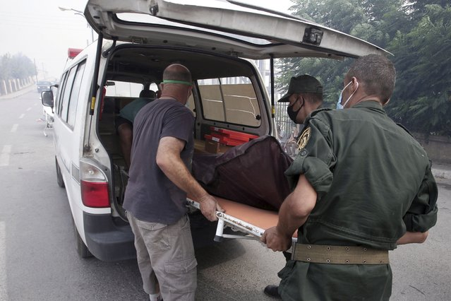 """Soldiers remove a dead man in a village near Tizi Ouzou some 100 km (62 miles) east of Algiers following wildfires in this mountainous region, Tuesday, August 10, 2021. Firefighters were battling a rash of fires in northern Algeria that have killed at least six people in the mountainous Kabyle region, the interior minister said Tuesday, accusing """"criminal hands"""" for some of the blazes. (Photo by Fateh Guidoum/AP Photo)"""