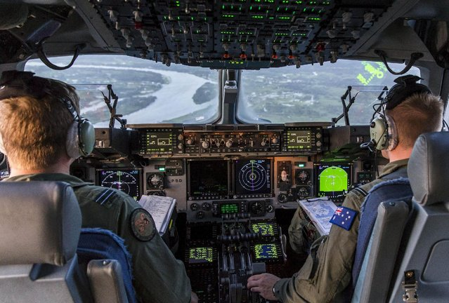 Royal Australian Air Force pilots Flight Lieutenant Simon Marshall (L) and Flying Officer Jake Nicholas prepare to land a C-17A aircraft loaded with supplies and assistance into Cyclone Winston-hit Suva, Fiji, February 22, 2016 in this handout image supplied by the Australian Department of Defence. (Photo by Reuters/Australian Department of Defence)