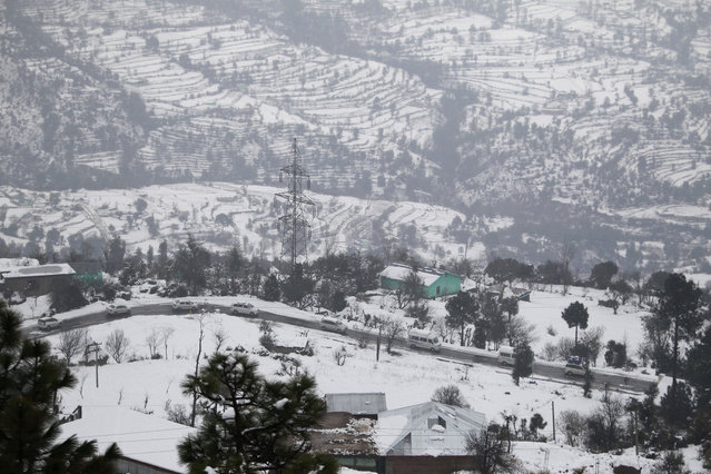 Stranded vehicle pass through a snow covered area on the Jammu-Srinagar highway in Kud, near about 90 kilometers (56 miles) east of Jammu, India, Monday, January16, 2017. The only all weather road link that connects the Kashmir valley to the rest of India was closed Monday due to heavy snowfall. (Photo by Channi Anand/AP Photo)