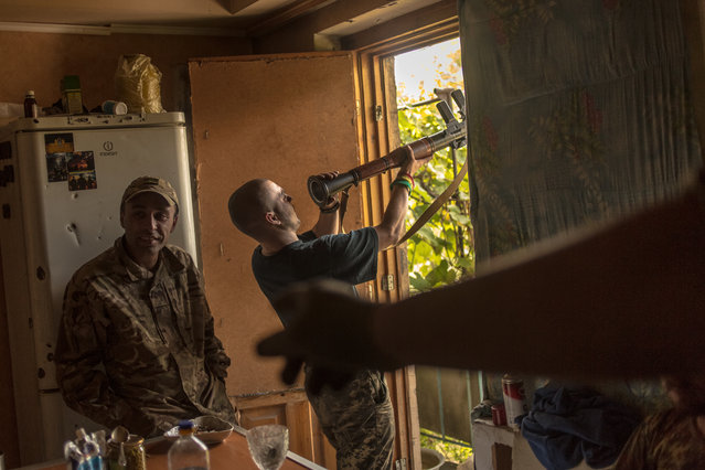 """Ukrainian volunteer """"Maliy"""" is cleaning up RPG after 2 failed attempts of shots during night clashes in Mariinka, Ukraine on October 4, 2016. (Photo by Anton Skybano/Radio Free Europe/Radio Liberty)"""