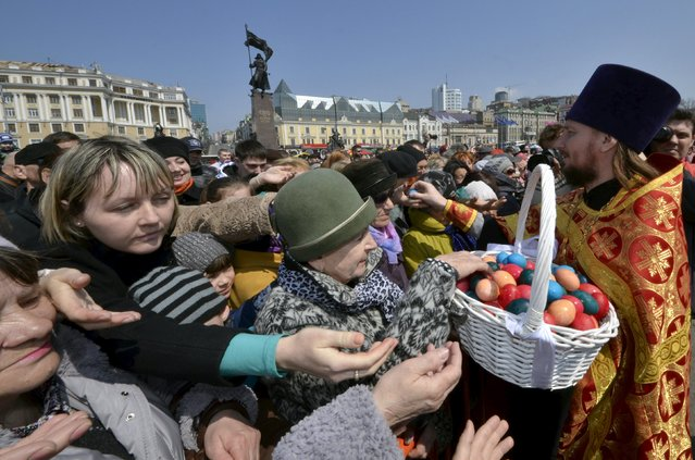 Believers take Easter eggs during the celebrations for the Orthodox Easter in the Russian far eastern city of Vladivostok, April 12, 2015. (Photo by Yuri Maltsev/Reuters)