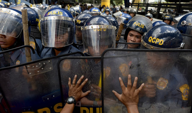 """An activist pushes the shields of policemen during a protest near the EDSA Shrine along a highway in Manila on February 25, 2016, commemorating the 30th anniversary of a bloodless popular revolt that ended the iron rule of late dictator Ferdinand Marcos in 1986. Philippine President Benigno Aquino urged voters on February 25 to stamp out the stunning political resurgence of Ferdinand Marcos' family, as the nation marked 30 years since a """"People Power"""" uprising toppled the late dictator. (Photo by Noel Celis/AFP Photo)"""