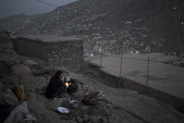 A woman cooks dinner outside her house in Kabul, Afghanistan, Saturday, September 11, 2021. (Photo by Felipe Dana/AP Photo)