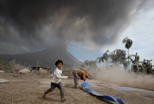 An Indonesian boy runs while playing as Mount Sinabung spews volcanic ash into the air during an eruption, at a farm in Sibintun, North Sumatra, Indonesia, Wednesday, January 15, 2014. (Photo by Binsar Bakkara/AP Photo)