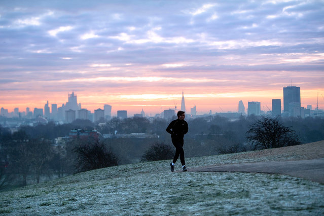 A man runs across a frosty Primrose Hill in London, UK at sunrise January 23, 2019. The Met Office issued yellow severe ice warnings for the south-east, central and north of England, as well as for Scotland. (Photo by Victoria Jones/PA Wire Press Association)