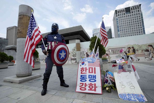 """A protester wearing a Captain America costume stands to support for the alliance between South Korea and the U.S. near the U.S. embassy in Seoul, South Korea, Friday, August 20, 2021. The signs read: """"The strength of the South Korea-U.S. alliance"""". (Photo by Ahn Young-joon/AP Photo)"""