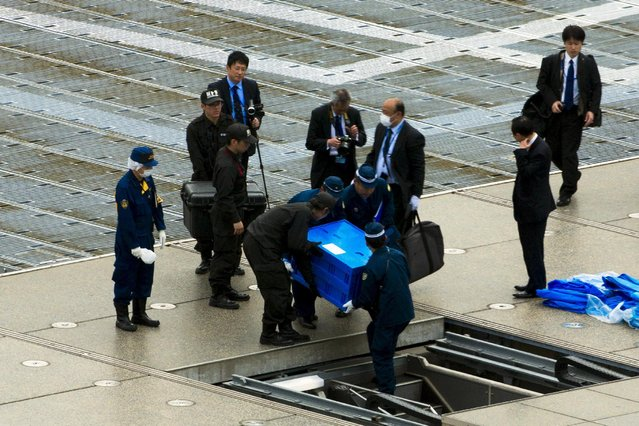 Officials carry a blue box that local media reported contains a drone from the rooftop of Prime Minister Shinzo Abe's official residence in Tokyo April 22, 2015. A drone marked with a radioactive sign landed on the rooftop of Japanese Prime Minister Shinzo Abe's office on Wednesday and later tested positive for small amounts of radiation, media reported. (Photo by Thomas Peter/Reuters)