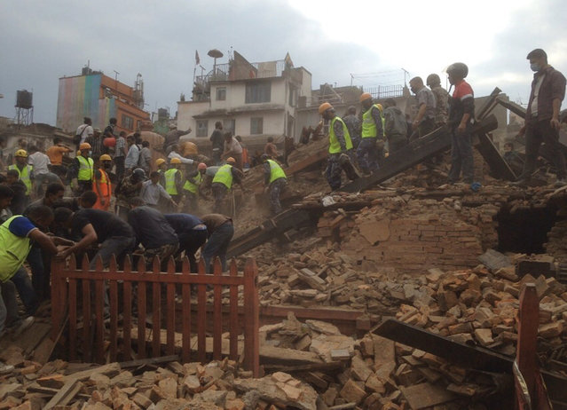 Rescuers clear the debris at Durbar Sqaure after an earthquake in Kathmandu, Nepal, Saturday, April 25, 2015. (Photo by Niranjan Shrestha/AP Photo)