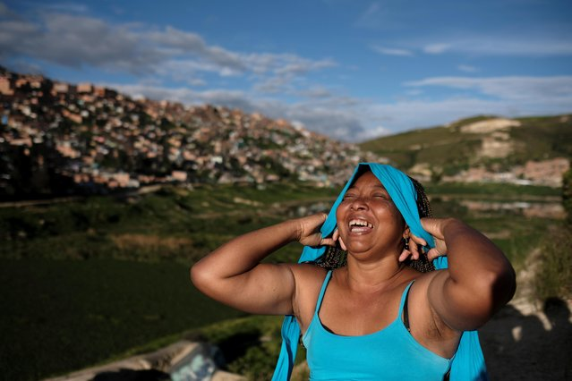 "Lina, who said she was raped by dozens of right-wing paramilitary fighters in the Montes de Maria region during the five-decade civil war, laughs as she puts on a hairband in Soacha, on the outskirts of Bogota, Colombia, June 12, 2018. Lina is determined to speak to the truth tribunal after she – and many women like her – was forced to remain silent during the conflict because paramilitary fighters controlled local authorities. ""I had to put on a mask to hide the pain that I felt from my child. After 22 years, I can declare the facts to the competent authorities"", she said. (Photo by Nacho Doce/Reuters)"