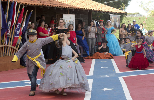 From the very old to the very young, descendants of American Southerners Wearing Confederate-era dresses and uniforms dance during a party to celebrate the 150th anniversary of the end of the American Civil War in Santa Barbara d'Oeste, Brazil, Sunday, April 26, 2015. (Photo by Andre Penner/AP Photo)