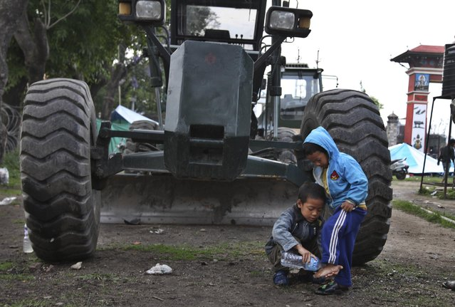 A young Nepalese boy washes the feet of his sibling next to an earth mover at a makeshift camp for the earthquake affected in Kathmandu, Nepal, Tuesday, April 28, 2015. (Photo by Altaf Qadri/AP Photo)