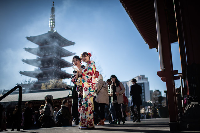 Two women wearing kimonos pose for pictures around Sensoji temple in the Asakusa district of Tokyo, on January 21, 2019. (Photo by Martin Bureau/AFP Photo)