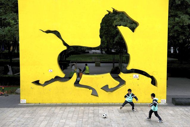 Children play soccer near an art installation depicting a horse at a residential building compound in Beijing, Tuesday, October 5, 2021. (Photo by Andy Wong/AP Photo)