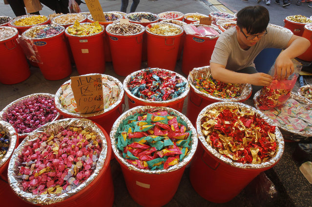 In this Tuesday, January 29, 2019, file photo, a vendor packs candies at the Dihua Street market in Taipei, Taiwan, Tuesday, Jan. 29, 2019. Taiwanese shoppers started hunting for delicacies, dried goods, and other bargains at the market ahead of the Lunar New Year celebrations which according to the lunar calendar will take place on Feb. 5. (Photo by Chiang Ying-ying/AP Photo)