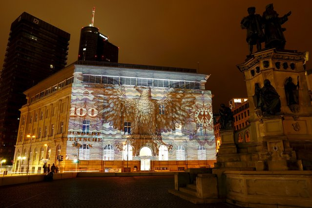 """A branch of Germany's largest business bank, Deutsche Bank AG, is illuminated with a banknote of Germany's former currency, Deutsche Mark, at the start of the """"Luminale, light and building"""" event in Frankfurt, Germany, March 12, 2016. (Photo by Kai Pfaffenbach/Reuters)"""