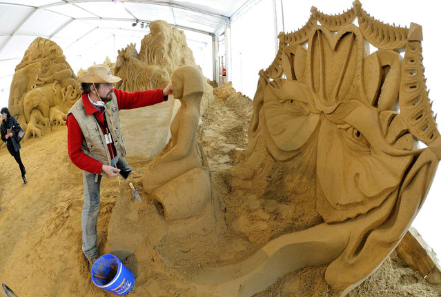 "Russian sculptor Dmitry Klimenko works on a sculpture made of sand during the ""1. Berliner Sandwelt"", festival and exhibition of sand sculptures, in Elstal, Germany, 29 April 2015. Twenty international artists used around 1,100 tons of sand to craft their sand sculptures presenting their artistic visions of Africa. The exhibition opens on 01 May. (Photo by Bernd Settnik/EPA)"