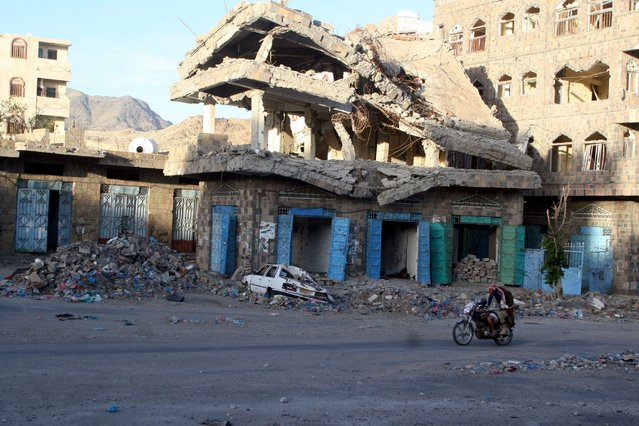 People ride a motorbike past a building destroyed during recent fighting in Yemen's southwestern city of Taiz March 14, 2016. (Photo by Anees Mahyoub/Reuters)