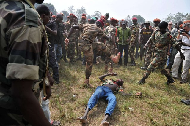 Members of the Central African Armed Forces (FACA) lynch to death a man suspected of being a former Seleka rebel on February 5, 2014, in Bangui. The impoverished former French colony descended into chaos last March when rebel forces overthrew the president, but an interim government lost control of the country. (Photo by Issouf Sanogo/AFP Photo)