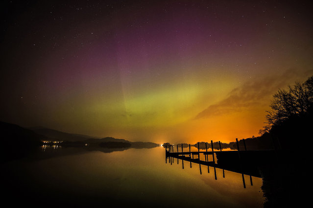 The aurora borealis, or the northern lights, over Derwent water near Keswick, England, Wednesday March 18, 2015. The northern lights are the result of collisions between gaseous particles in the Earth's atmosphere with charged particles released from the sun. (Photo by Owen Humphreys/AP Photo/PA Wire)