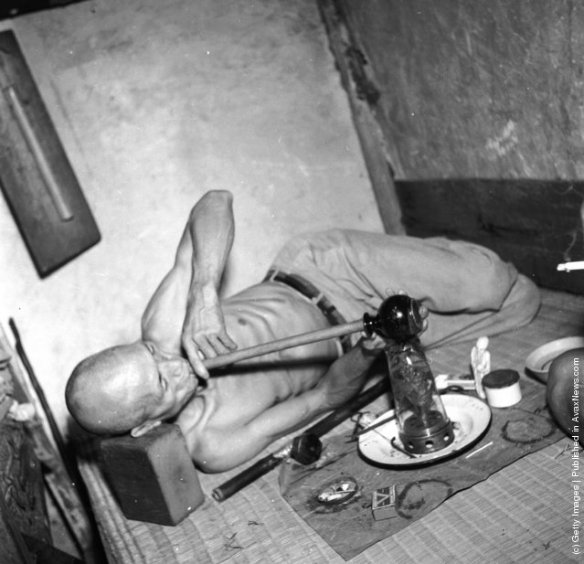 circa 1955:  A narcotic addict in the British Crown Colony of Hong Kong smokes from a home-made hookah pipe made of an earthen jug and a bamboo stick