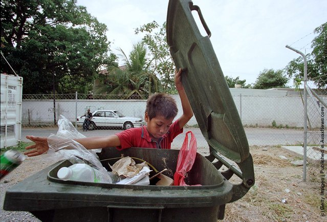 An East Timorese boy picks through the trash can at a local hotel looking for cans to recycle