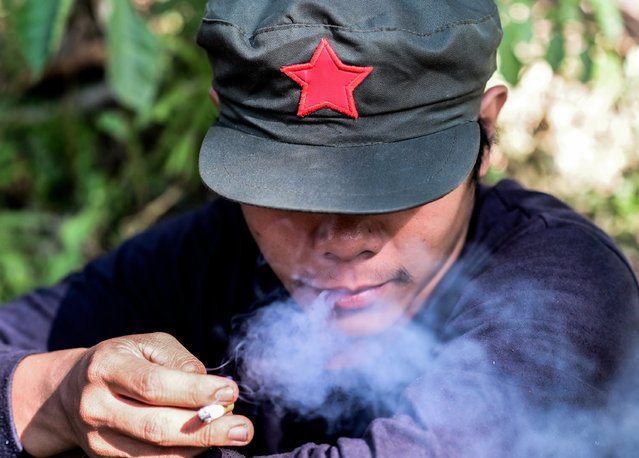 A fighter of the New People's Army-Melito Glor Command (NPA-MGC) smokes a cigarette at an undisclosed location in the mountains of Sierra Madre, Philippines, 31 March 2019. The rebels have negotiated unsuccessfully with five Filipino presidents before the current leader, Rodrigo Duterte. The NPA had about 60 fighters, nine automatic rifles and 26 single-shot rifles and pistols when it was established in 1969, before gradually growing and expanding. (Photo by Alecs Ongcal/EPA/EFE)