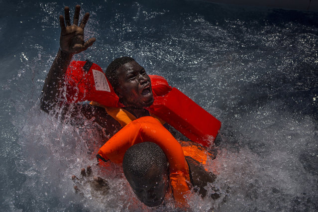 A handout photo made available by the World Press Photo (WPP) organization on 13 February 2017 shows a picture by British photographer Mathieu Willcocks that won the Spot News – Third Prize, Stories award of the 60th annual World Press Photo Contest, it was announced by the WPP Foundation in Amsterdam, The Netherlands on 13 February 2017. Caption: Two men panic and struggle in the water during their rescue. Their rubber boat was in distress and deflating quickly on one side, tipping many migrants in the water. They were quickly reached by rescue swimmers and brought to safety. (Photo by Mathieu Willcocks/EPA/World Press Photo)