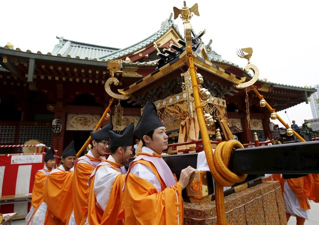 Shinto studies specialty students in traditional costumes push a Horen, a portable shrine, after a ritual during the Kanda festival at the Kanda-Myojin shrine in Tokyo May 9, 2015. (Photo by Toru Hanai/Reuters)