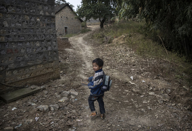 """""""Left behind"""" child Luo Lie,5, right, walks home from school on December 16, 2016 in Anshun, China. (Photo by Kevin Frayer/Getty Images)"""