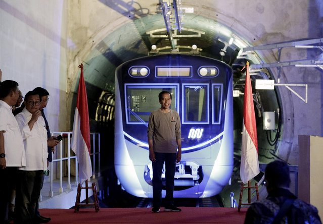 """Indonesian President Joko """"Jokowi"""" Widodo, center, stands on a stage with the background of a Jakarta Mass Rapid Transit train during the inauguration ceremony of the subway line in Jakarta, Indonesia, Sunday, March 24, 2019. The 16-kilometer (10-mile) line system running south from Jakarta's downtown is the first phase of a development that if fully realized will plant a cross-shaped network of stations on the teeming city of 30 million people. (Photo by Dita Alangkara/AP Photo/Pool)"""