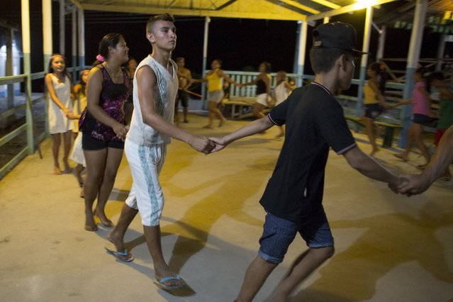 Kambeba Indian, Dream Braga (C), 18, dances with friends at the village Tres Unidos, Amazon state May 9, 2015. (Photo by Bruno Kelly/Reuters)