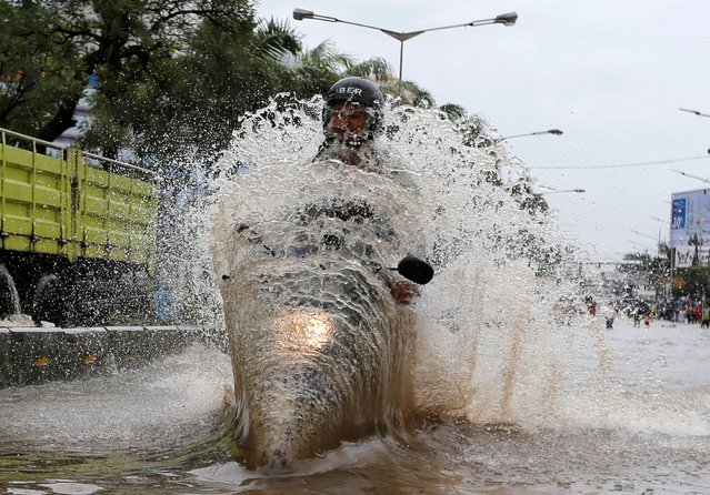A man drives a motorcycle through floodwaters in a flood-hit area at the Mangga Dua business district in Jakarta, Indonesia February 21, 2017. (Photo by Reuters/Beawiharta)