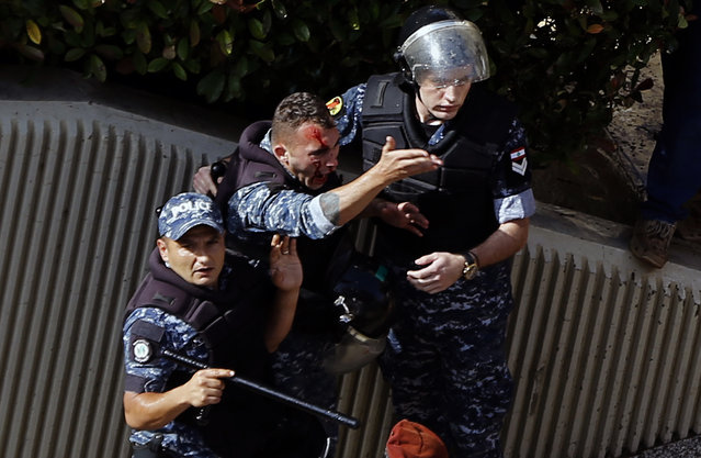 """An injured police officer shouts during a protest in Beirut, Lebanon, Monday, May 20, 2019, as the government faces a looming fiscal crisis. Over one hundred protesters gathered Monday outside the Government House in downtown Beirut shouting """"Thieves, thieves!"""" as the Cabinet met for its 16th session to reach agreement on controversial budget cuts. (Photo by Bilal Hussein/AP Photo)"""