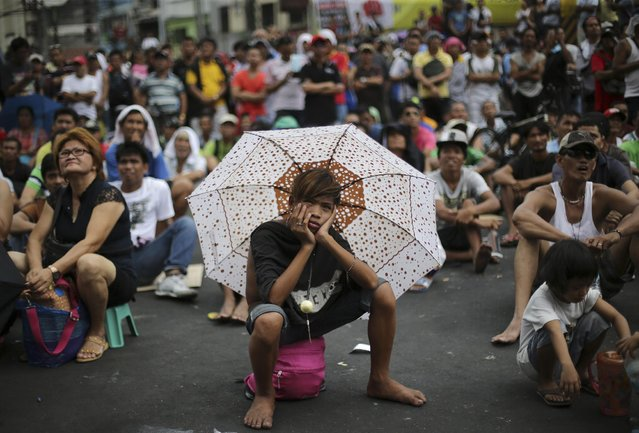 A Filipino uses an umbrella to shield him from the sun as they watch a live satellite feed of the welterweight title fight between Filipino boxing hero Manny Pacquiao and Floyd Mayweather Jr. during a free public viewing in downtown Manila, Philippines on Sunday, May 3, 2015. Mayweather Jr. won the match. (Photo by Aaron Favila/AP Photo)
