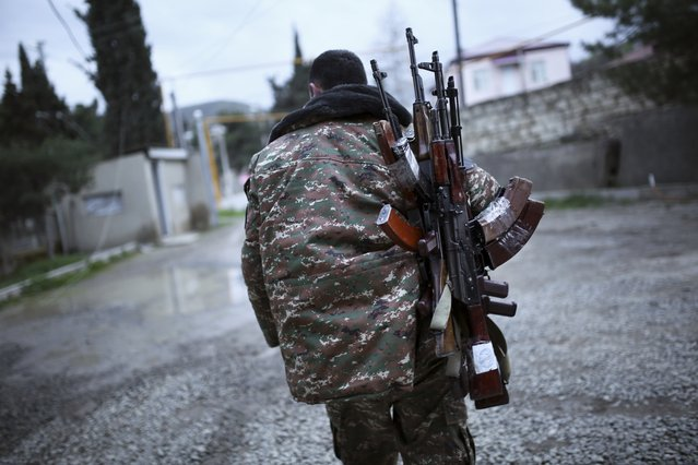 An ethnic Armenian fighter carries Kalashnikov machine guns to his comrade-in-arms at Martakert province in the separatist region of Nagorno-Karabakh, Azerbaijan, Monday, April 4, 2016. (Photo by Vahan Stepanyan/PAN Photo via AP Photo)