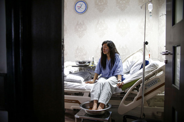 "Indian Everest climber Ameesha Chauhan rests on her bed as she dips her frost-bitten feet in a warm solution at a hospital in Kathmandu on May 27, 2019. Ameesha Chauhan, a survivor of the Everest ""traffic jam"" who is in hospital recovering from frostbite, said climbers without basic skills should be barred to prevent a recurrence of this year's deadly season on the world's highest peak. (Photo by Gopen Rai/AFP Photo)"