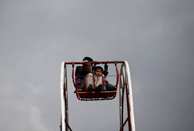 A boy reacts as he rides a ferris wheel during the Afghan New Year (Newroz) celebrations in Kabul March 21, 2014. (Photo by Ahmad Masood/Reuters)
