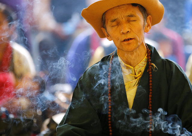 """Smoke rise from the burning incense as a Tibetan man in traditional attire offers prayer during a function organised to mark """"Losar"""", or the Tibetan New Year, in Kathmandu, Nepal March 1, 2017. (Photo by Navesh Chitrakar/Reuters)"""