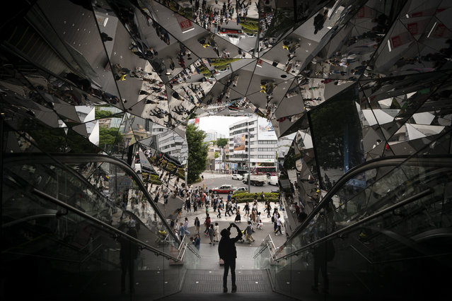 A tourist takes pictures in the entrance way to a shopping mall decorated with mirrors Saturday, May 18, 2019, in Harajuku district of Tokyo. (Photo by Jae C. Hong/AP Photo)