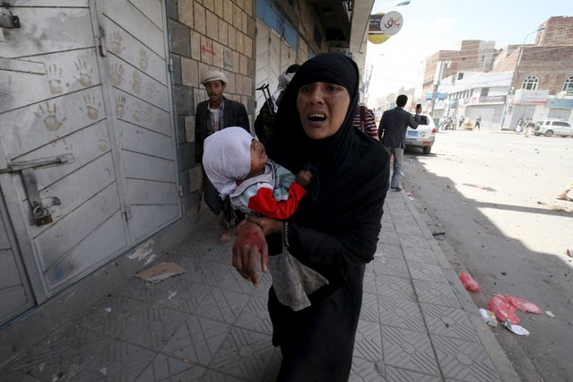 An injured woman carrying a child reacts after air strikes hit the house of Yemen's former President Ali Abdullah Saleh in Sanaa May 10, 2015. (Photo by Mohamed al-Sayaghi/Reuters)
