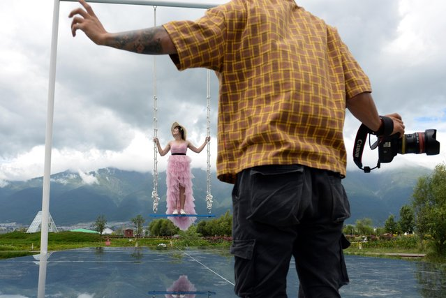 A photographer directs Zhang Xiaoxia as she poses on a swing above a mirror platform near Erhai Lake in Dali Bai Autonomous Prefecture, Yunnan province, China on June 15, 2019. (Photo by Tingshu Wang/Reuters)