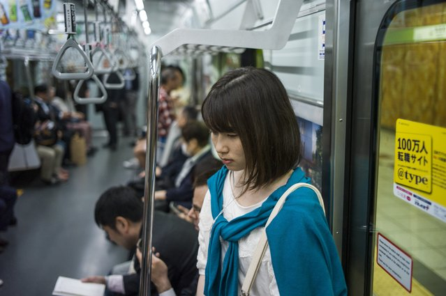 A commuter rides the subway at Shinjuku station in Tokyo on May 11, 2015. (Photo by Fred Dufour/AFP Photo)